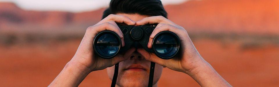 Een man kijkt met een verrekijker naar de toekomst